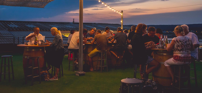 Terrasse du restaurant remplie de clients avec le coucher de soleil en arrière plan